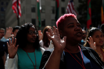 Citizenship candidates raise their hands during the Pledge of Allegiance during the U.S. Citizenship and Immigration Services (USCIS) naturalization ceremony at Rockefeller Plaza in New York City