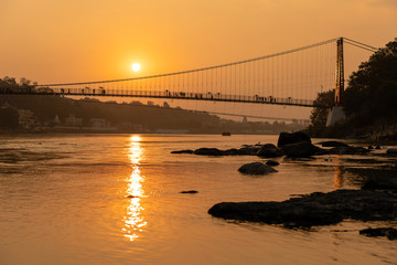 Beautiful view of Ganges river embankment and bridge at sunset. Rishikesh, India Wall mural