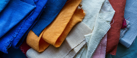 Foto op Plexiglas Stof A stack of colorful fabrics background. Multicolored linen fabric