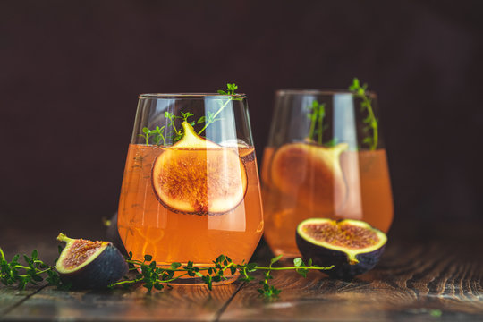 Pink cocktail with fig, thyme and ice in glass on dark wooden background, close up