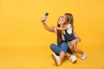 Woman in light clothes doing selfie with cute child baby girl 4-5 years old. Mommy little kid daughter isolated on yellow background studio portrait. Mother's Day family parenthood childhood concept.