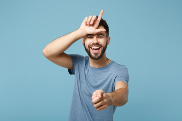Young laughing man in casual clothes posing isolated on blue wall background, studio portrait. People lifestyle concept. Mock up copy space. Showing loser gesture, pointing index finger on camera.