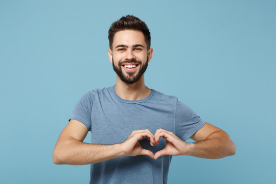 Young smiling handsome man in casual clothes posing isolated on blue wall background, studio portrait. People lifestyle concept. Mock up copy space. Showing shape heart with hands, heart-shape sign.