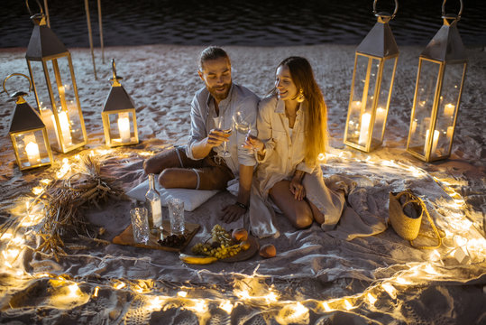 Couple having a romantic dinner, hugging and clinking wine glasses at the beautifully decorated place illuminated with different lights the sandy beach at dusk