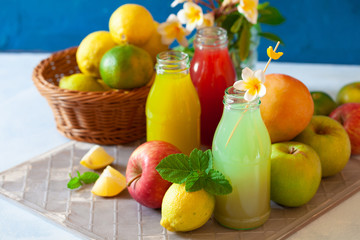 Fresh fruit, berry and vegetable juices on bright blue background.Homemade refreshing beverage