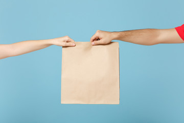 Close up cropped hands hold brown clear empty blank craft paper bag box food for takeaway isolated on blue background. Packaging template mock up. Delivery service concept. Copy space Advertising area