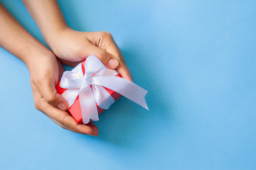 Gift in female hands. Woman hands holding a giftbox, present or surprise