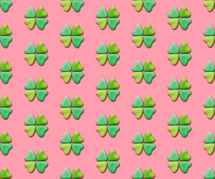 Heart-shaped candies re-arranged in a clover shape on a pink background