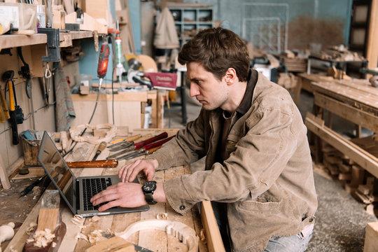 Artisan using laptop in the shop