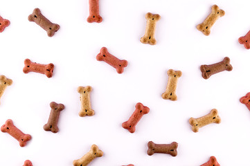 Dog food pattern made with dry snacks in shape of bones. Funny cute flat lay texture. Home pets, animals feeding. Special diet, training supply.
