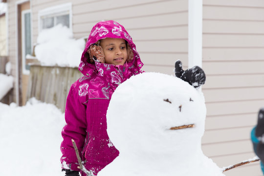 Child happily building a snowman outside in the snow while dressed warmly in coats and mitts