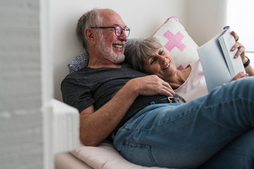Elderly couple reading a book at home