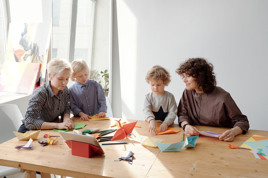 Kids making origami with parents
