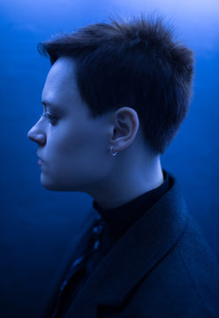 Profile of woman with short hair in blue light