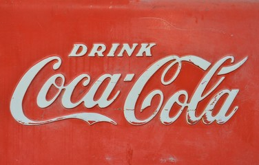 Rolla, Missouri - July 18, 2017: Sign of Coca-Cola painted in a rusty and old metal. Coca-Cola is a carbonated soft drink produced by The Coca-Cola Company.