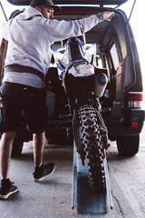 Man loads his motocross bike into his van