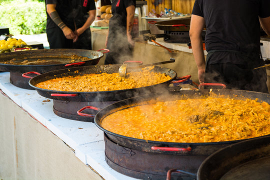 Paella served from paella dishes on a street food festival.