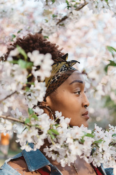 A beautiful young black woman standing amongst the cherry blossom trees