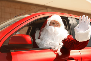 Authentic Santa Claus driving his modern car, outdoors