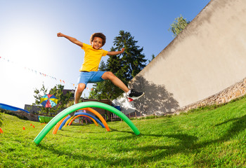 Happy cute boy jump over barriers on playground