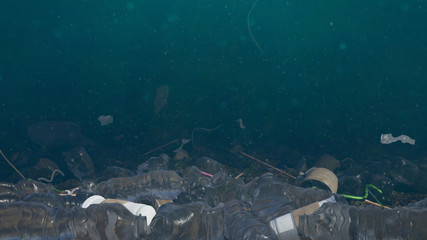 plastic pollution in ocean water, bottles and bags on the sea floor, micro plastic pollution