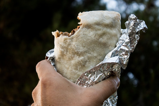 Holding a Burrito with a Bite Out of It in California