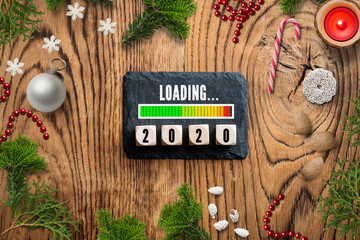 """slate plate with message """"loading 2020"""", surrounded by christmas decoration on wooden background"""