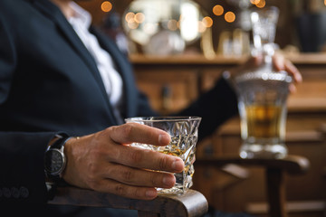 Male hand with a glass of expensive whiskey