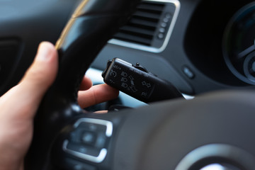 Close-up of male hand, presses signal switch button in the car.