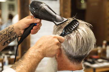 Hairdresser making stylish haircut for a handsome old man