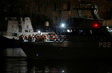 Migrants who were rescued by the Italian coastguard arrive on an Armed Forces of Malta patrol boat in Valletta's Marsamxett Harbour