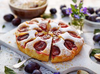 Plum cake, traditional homemade  cake with fruit, divided into portions, sprinkled with powdered...