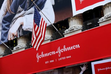 The U.S. flag is seen over the company logo for Johnson & Johnson to celebrate the 75th anniversary of the company's listing at the NYSE in New York