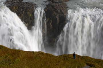 A tourist takes a selfie photograph in an area forbidden to walking, overlooking the waterfalls in Gullfoss