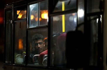 Migrants who were rescued by the Italian coastguard sit in a police bus as it leaves from the Armed Forces of Malta Maritime Squadron base in Valletta's Marsamxett Harbour