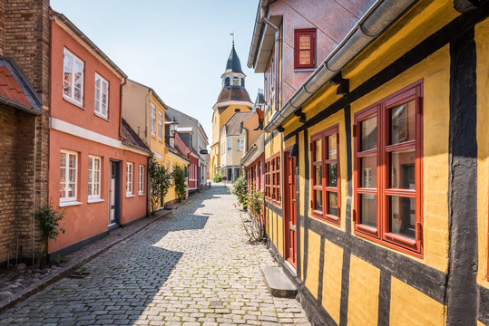 An alleyway with cobblestones and half timbered houses, leading up to the church in Faaborg