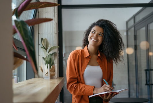 Student studying, learning language, exam preparation at modern library, education concept. Cheerful business woman planning start up project, taking notes, working in office. Successful business