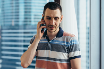 Businessman holding smartphone standing by the window in office