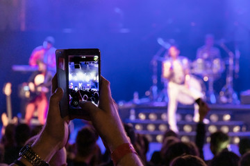 Man's hands holding a cell phone while filming a music band at the concert