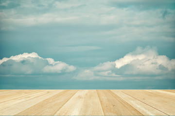 Wooden table top on blue sky with clouds for background