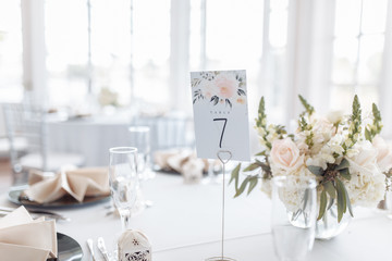 White, peach and muted green wedding table decorations with floral arrangements, green plates, glasses, silverware, peach napkins and table numbers.