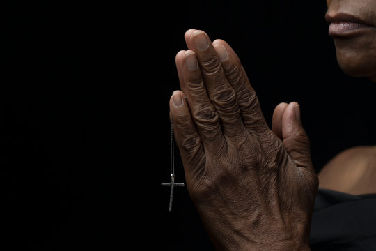 Religious and elderly african-american woman faithfully praying with hope while holding a cross