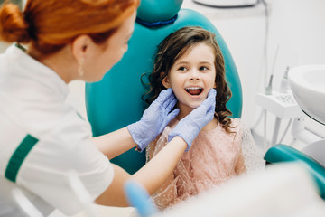 Portrait of a lovely little kid showing teeth to the pediatric dentist.