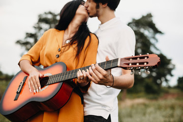 Hands of a young couple holding a guitar while kissing outside in nature.