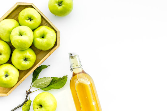 Apple cider in bottle near tray with fruits on white background top view copy space