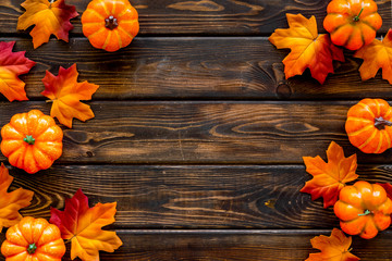 Autumn frame with colorful leaves and pumpkins on dark wooden top view copy space