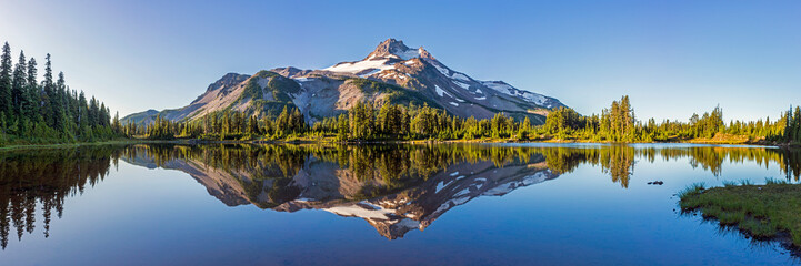Volcanic mountain in morning light reflected in calm waters of lake.
