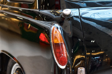 Poster Vintage voitures Closeup of a black vintage car. Back view part of retro car
