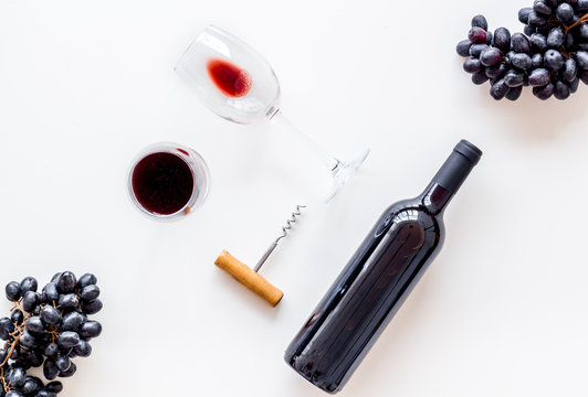 Red wine bottle near wineglass on white background top view copy space