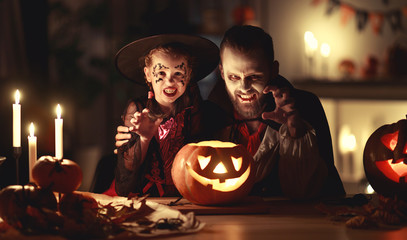 happy family   father and child daughter in costumes and makeup on  Halloween